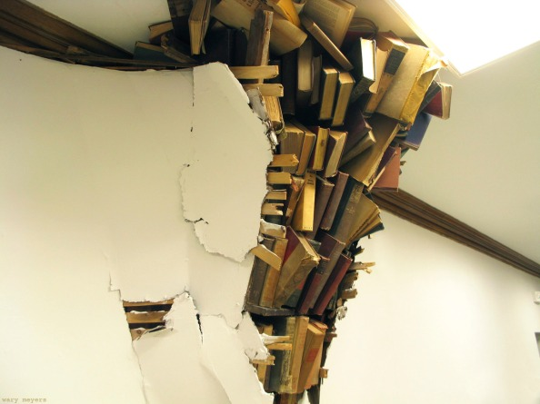 Photograph of a wall that has broken open ostensibly under the weight of a pile of books