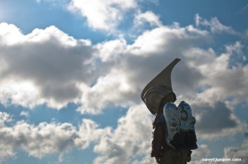 kid with helmet and rocket on back against backdrop of cloudy sky
