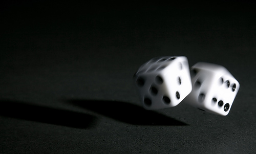 Image of two dice rolling in mid-flight