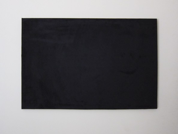 blank black canvas hanging on a cream wall