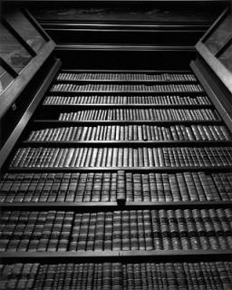 black and white photograph of a tall bookshelf filled with old-fashioned bound book. One book is pulled out a tiny bit.