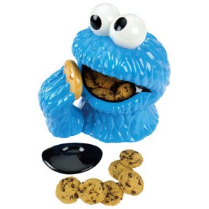Cookie jar shaped like the cookie monsters head, with the cookies in his mouth and a hand reaching up to feed him another cookie