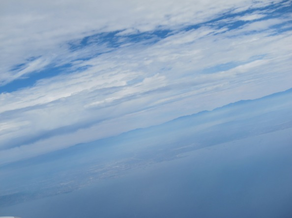 View of California from plane window. With layers of cloud in shades of blue and white down over the mountains, coastline and ocean.