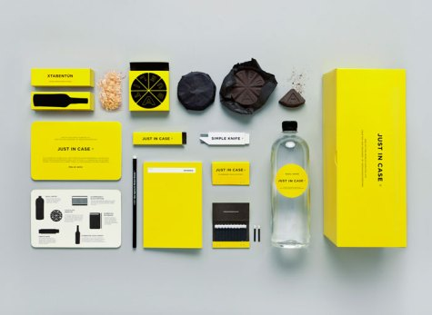 Just in Case kit laid out in bright canary yellow. Showing a bottle of water, knife, alcohol, chocolate, notebook, pen, matches and guide book.
