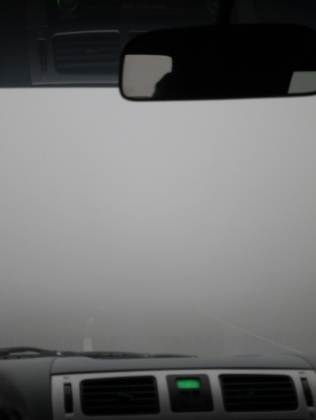 view from interior of car of a street disappearing into fog a couple of metres from the bumper