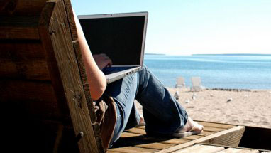 girl sitting on a reclining hair, laptop in lap, beach and sea in the background