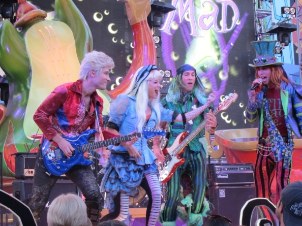 The Mad T Party Band in concert - featuring the white rabbit (guitar), Alice (vocals), the march hare (bass) and the mad hatter (lead vocals).