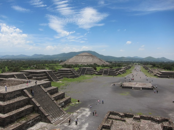 View from the top of the temple of the moon pyramid at Teotihuacán, along the Avenue of the dead, including the temple of the sun to the left and multiple small structures in the foreground