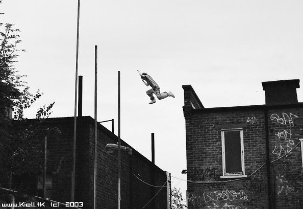 Black and white photograph of someone leaping a significant gap between the roofs of two brick buildings.