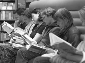 row of people sitting and reading what appears to be the same book