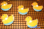 Cookies in the shape of ducklings with a line of blue at the bottom as though they are swimming.