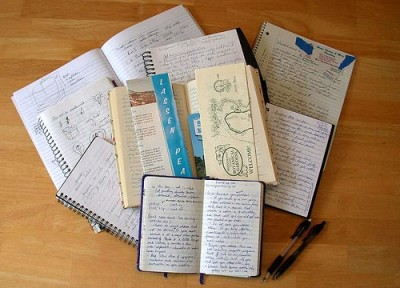 Pile of open hand written and hand drawn notebooks.