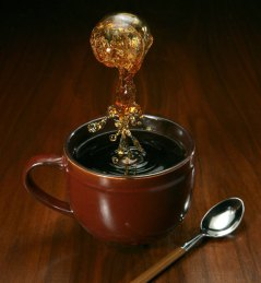 Cup of black coffee on a wooden table with a dramatic splash of coffee above it.