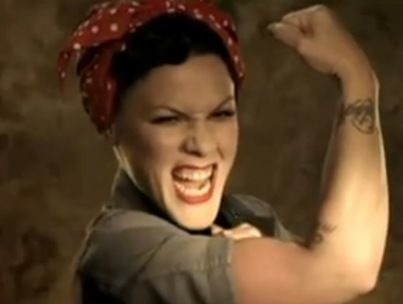 Pink doing a pose reminiscent of the 1940s propaganda campaign image 'Rosie the Riveter'. A young woman in a blue work shirt and red bandanna with white spots, holding up her arm to show her bicep, and implicitly, her strength. The caption on the original image reads 'we can do it', while it is not visible here, this image is taken from the video clip for the song 'raise your glass'