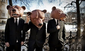 Image of the Teddybears (band). Three guys in suits and ties, looking casual, wearing bear heads.