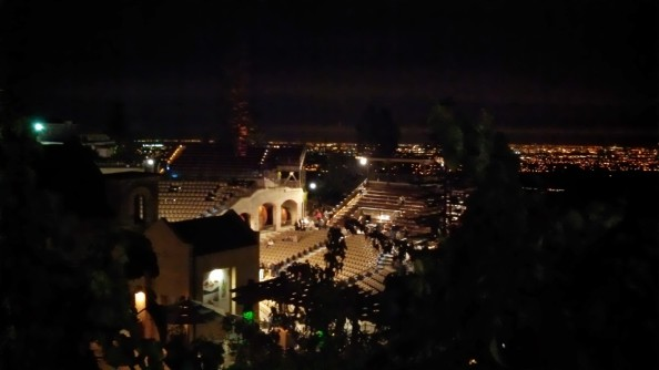 View across the amphitheatre at night, with the lights of the city in the background.