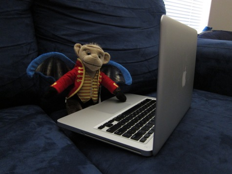 Foot-high Chistery (flying monkey from Wizard of Oz) sitting on a blue couch with a laptop on his lap.