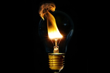 Incandescent light bulb on fire with the flame escaping the glass.