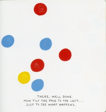 A number of dots, red, blue and yellow are strewn untidily across the page. The text says: THERE. WELL DONE. NOW TILT THE PAGE TO THE LEFT... JUST TO SEE WHAT HAPPENS.