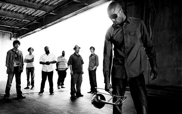 Black and white image of Trombone Shorty with his trombone and his band Orleans Avenue in the background