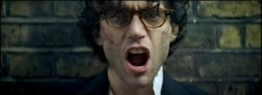 "Screen shot from Mika's music video ""Kick-Ass"". Mika standing defiant against a brick wall in blood and dirt as though he's recently been roughed up."