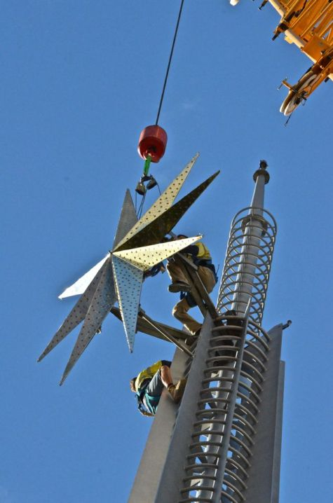 Two people in workman's gear perched on top of the Perth bell tower as a crane lowers the Christmas star into place