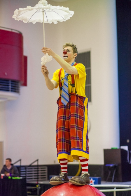 Rather concerned looking clown balancing on a large rubber ball and uncertainly holding a frilly white umbrella.