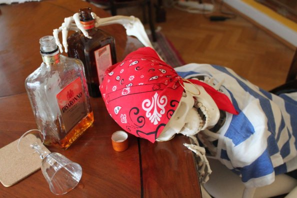 Skeleton dressed as a pirate, slumped over a table, one hand still wrapped around one of the mostly empty bottles of alcohol arrayed in front of him. Or her. But probably him.