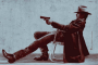 Guy in profile. He sits leaning way back in a grungy folding chair. He's wearing a long coat, riding boots and a cowboy hat low over his eyes. And he's got a gun aimed straight and steady at someone out of sight. (Timothy Olyphant as Raylan Givens in Justified)